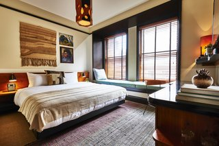 The guest rooms combine artwork, textiles, and rich wood tones to provide a luxurious, cozy retreat.