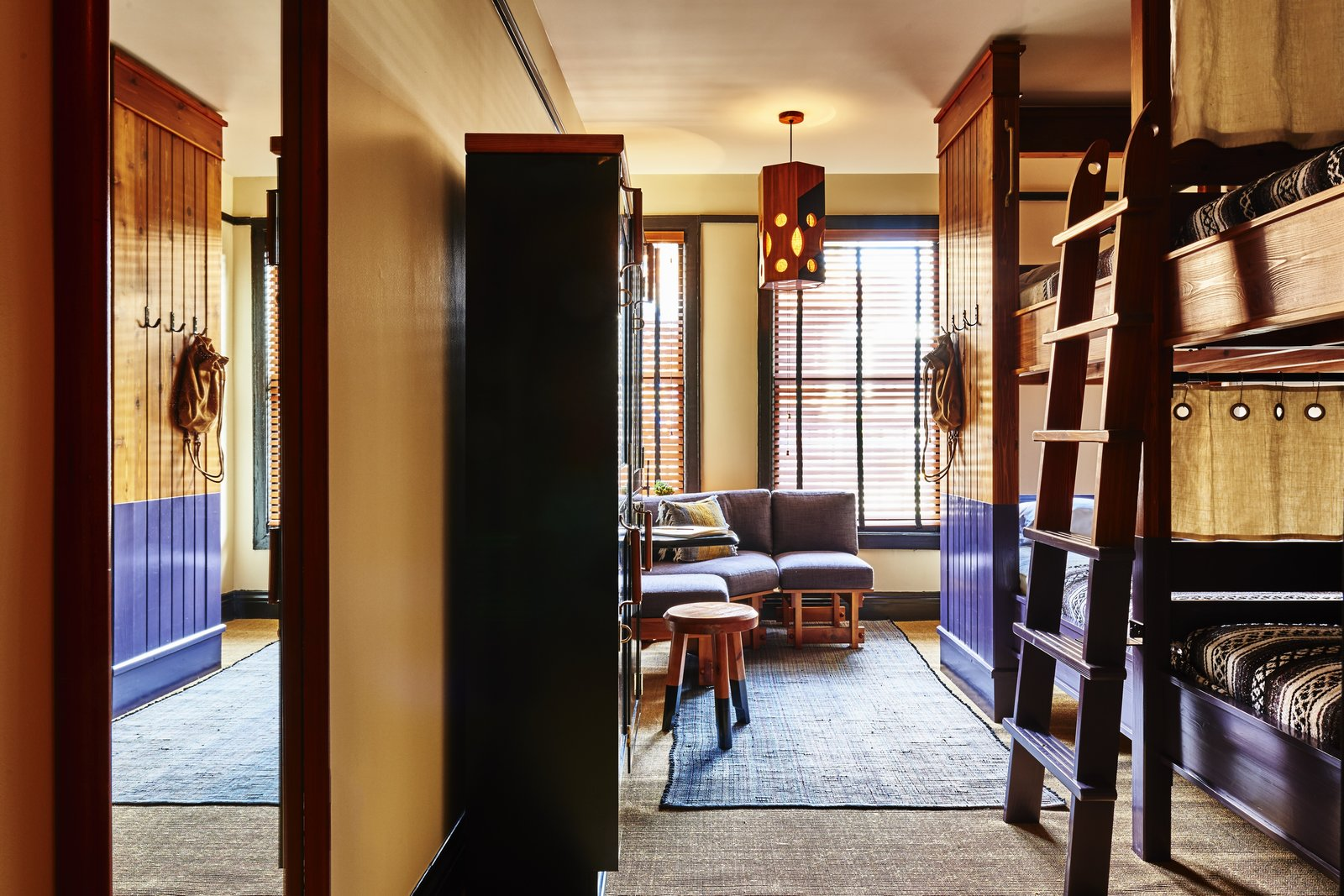 Bedroom The shared rooms, the most affordable and popular option, are inventive in decor with bunk beds, draperies, and accents of purple.  Photo 9 of 10 in A 1920s Office Building Is Revamped as a Craftsman-Inspired Hotel in Los Angeles