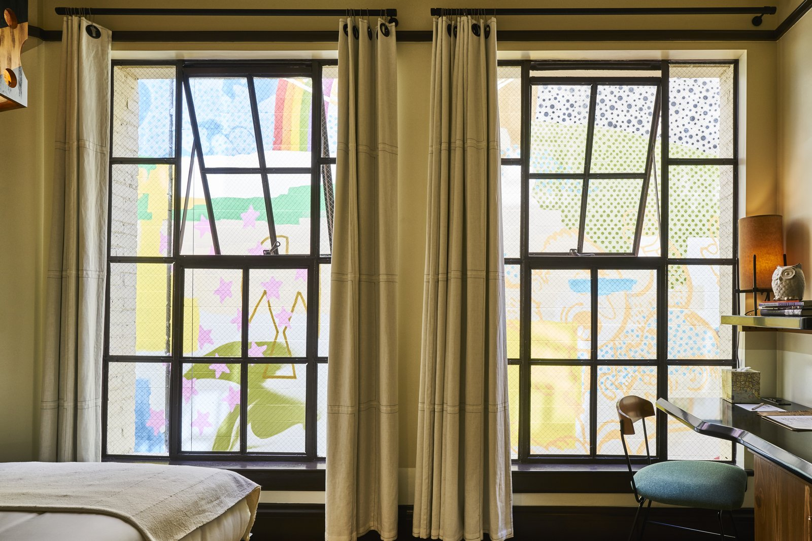 Bedroom, Bed, Table Lighting, Chair, and Lamps A desk looks out at a colorful mural, a reminder of L.A.'s dynamic surroundings.  Photo 8 of 10 in A 1920s Office Building Is Revamped as a Craftsman-Inspired Hotel in Los Angeles