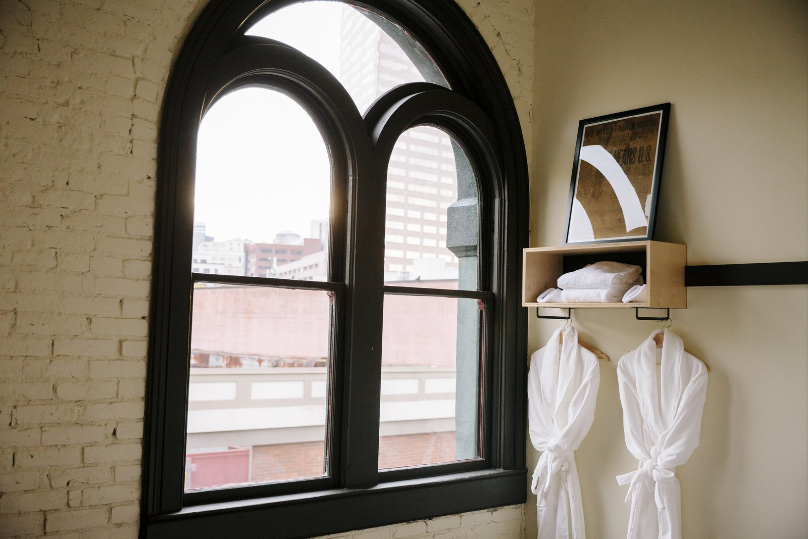 Bedroom, Storage, and Shelves The orginal dark wood window frames and exterior brick walls remain in tact. Simple, modern additions provide amenities in the guest rooms.  Photo 9 of 11 in A Chic Portland Hotel Offers Lodging As Affordable as $35 a Night