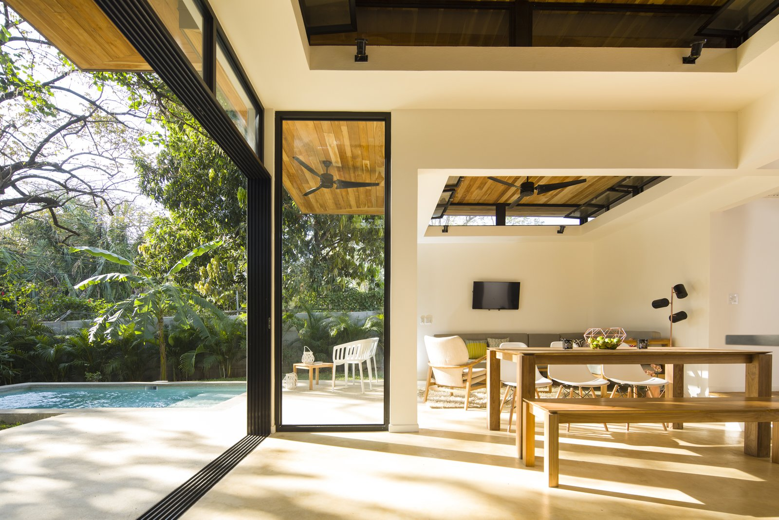 Dining Room, Floor Lighting, Chair, Wall Lighting, and Bench Large, operable glass doors and clerestory windows provide a fluid transition between the interior retreat and the exterior landscape.  Photo 5 of 11 in Decompress at This Boutique Hotel and Yoga Retreat in the Costa Rican Jungle