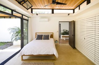 Similar to the open spaces, the sleeping quarters have operable, sliding glass doors and clerestory windows that allow the tropical air to freely pass between the exterior and interior.
