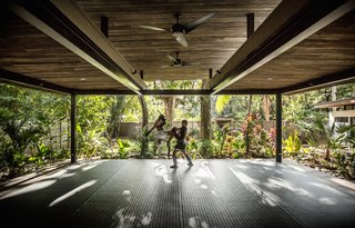 The yoga studio is surrounded on all sides by the jungle.  Light, shadows, and wind pass through the open structure.