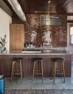 In the kitchenette area, seamless walnut cabinets, poured concrete countertops, and glazed brick tiles introduce minimalistic, modern elements.