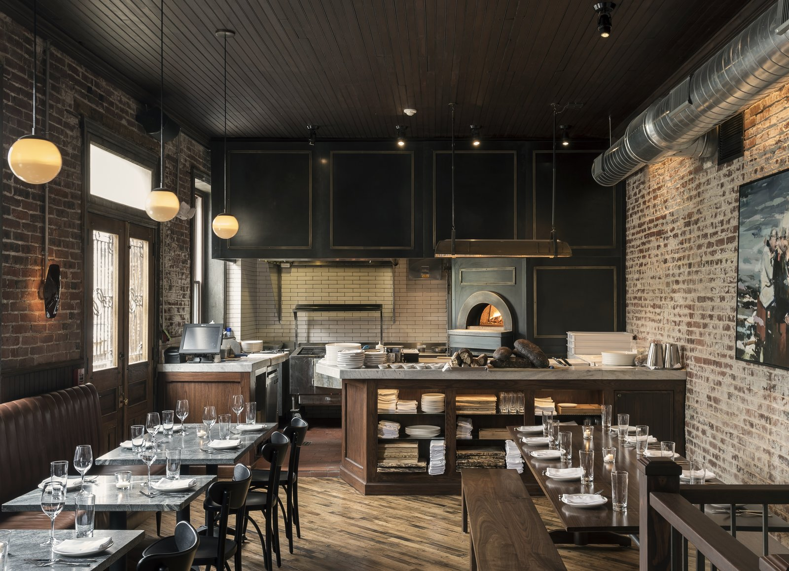 Dining Room, Table, Chair, Bench, Medium Hardwood Floor, Pendant Lighting, Wall Lighting, and Ceiling Lighting An open kitchen concept connects the wood fired oven with the communal dining room.  Photo 9 of 11 in History and Modernity Meet in This Industrial Hotel and Restaurant in Philadelphia