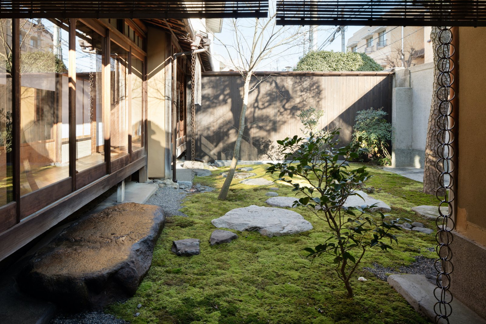 Outdoor, Garden, Trees, Gardens, Grass, Boulders, Wood Fences, Wall, Vertical Fences, Wall, and Concrete Fences, Wall A lounge space looks onto a calming moss garden and provides the perfect zen setting to relax with a cup of tea.  Photo 3 of 13 in A Minimalist Townhouse Provides Serene Accommodations in Historic Kyoto