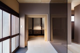 A Minimalist Townhouse Provides Serene Accommodations in Historic Kyoto - Photo 5 of 12 - Clean lines and sophisticated colors with reds, purples, and browns fill the interior.  An office space with a desk and couch is provided on the first floor.