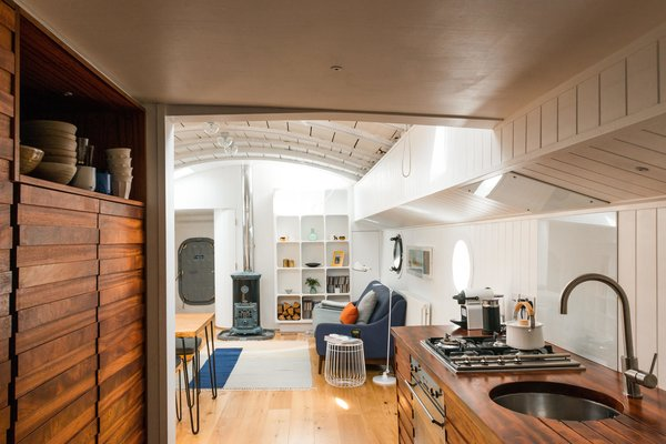 Light Hardwood Floor, Living Room, and Sofa A Saikai Kaico Japanese enamel kettle and hand thrown dishes by David Green Ceramics sit proudly in the galley kitchen.  Photo 4 of 9 in Londoners Can Live in This Scandinavian-Inspired, Converted Barge For $424K