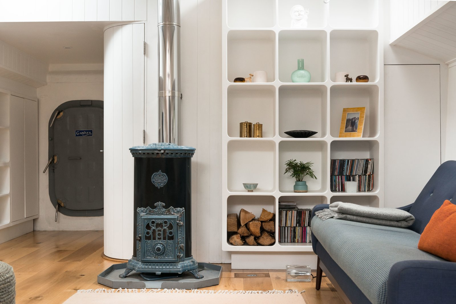 Living Room, Light Hardwood Floor, Shelves, Wood Burning Fireplace, and Sofa An original 1920's restored Goodin Woodburning Stove anchors the cozy living space.  Photo 5 of 9 in Londoners Can Live in This Scandinavian-Inspired, Converted Barge For $424K