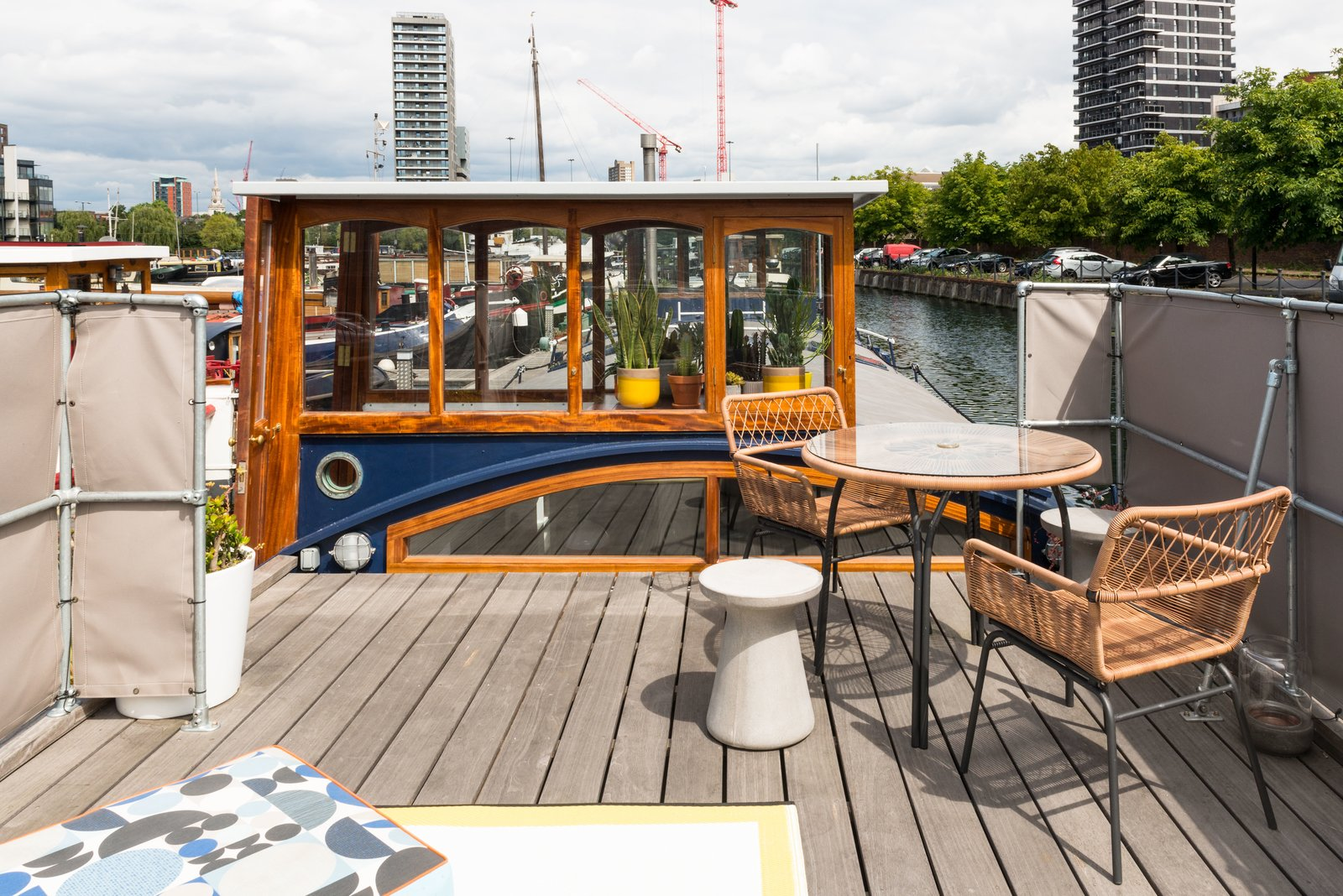 Outdoor, Rooftop, and Wood Patio, Porch, Deck A round concrete stool, table and chairs, custom cushions, and outdoor rug create a perfect terrace setting to look out to the city beyond.  Photo 9 of 9 in Londoners Can Live in This Scandinavian-Inspired, Converted Barge For $424K