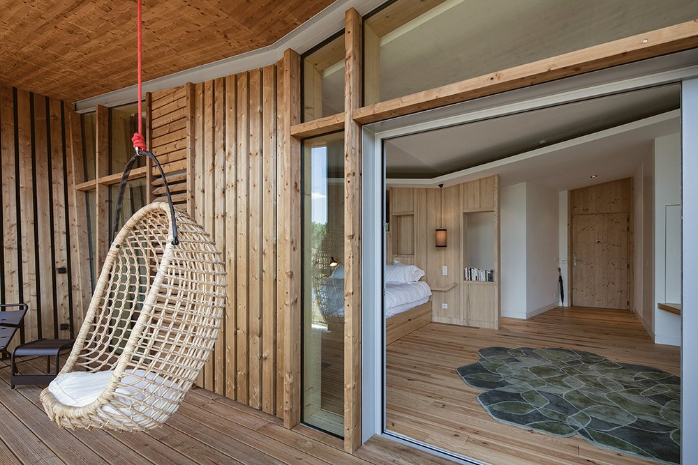 Small Patio, Porch, Deck, Wood Patio, Porch, Deck, Bedroom, Bed, Light Hardwood Floor, Pendant Lighting, Rug Floor, and Shelves  Photo 6 of 10 in Harmonizing With Nature, These Eco-Huts Offer Respite in the Heart of France