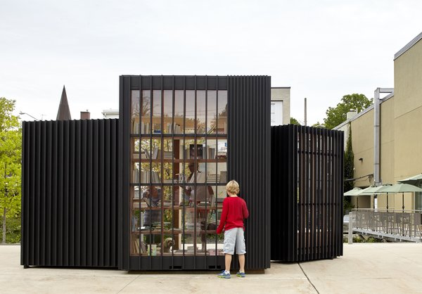 Widely spaced vertical wood slats anchor attention to the stacks of books arranged on the interior.