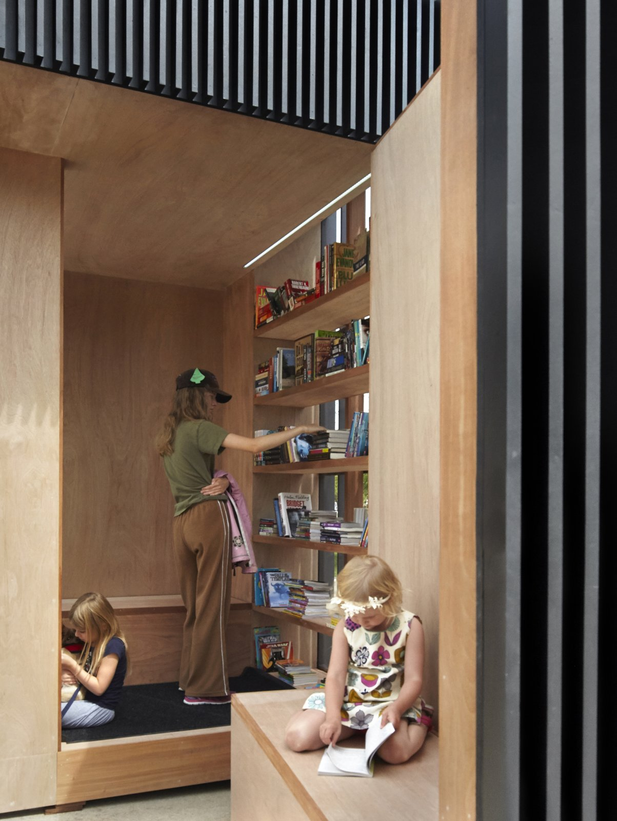 Wrapped in marine grade veneer plywood, the interior walls frame a warm oasis for reading and viewing.  Photo 6 of 8 in Toronto's Story Pod Doubles as a Lending Library and Community Hub