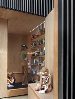 Toronto's Story Pod Doubles as a Lending Library and Community Hub - Photo 5 of 7 - Wrapped in marine grade veneer plywood, the interior walls frame a warm oasis for reading and viewing.