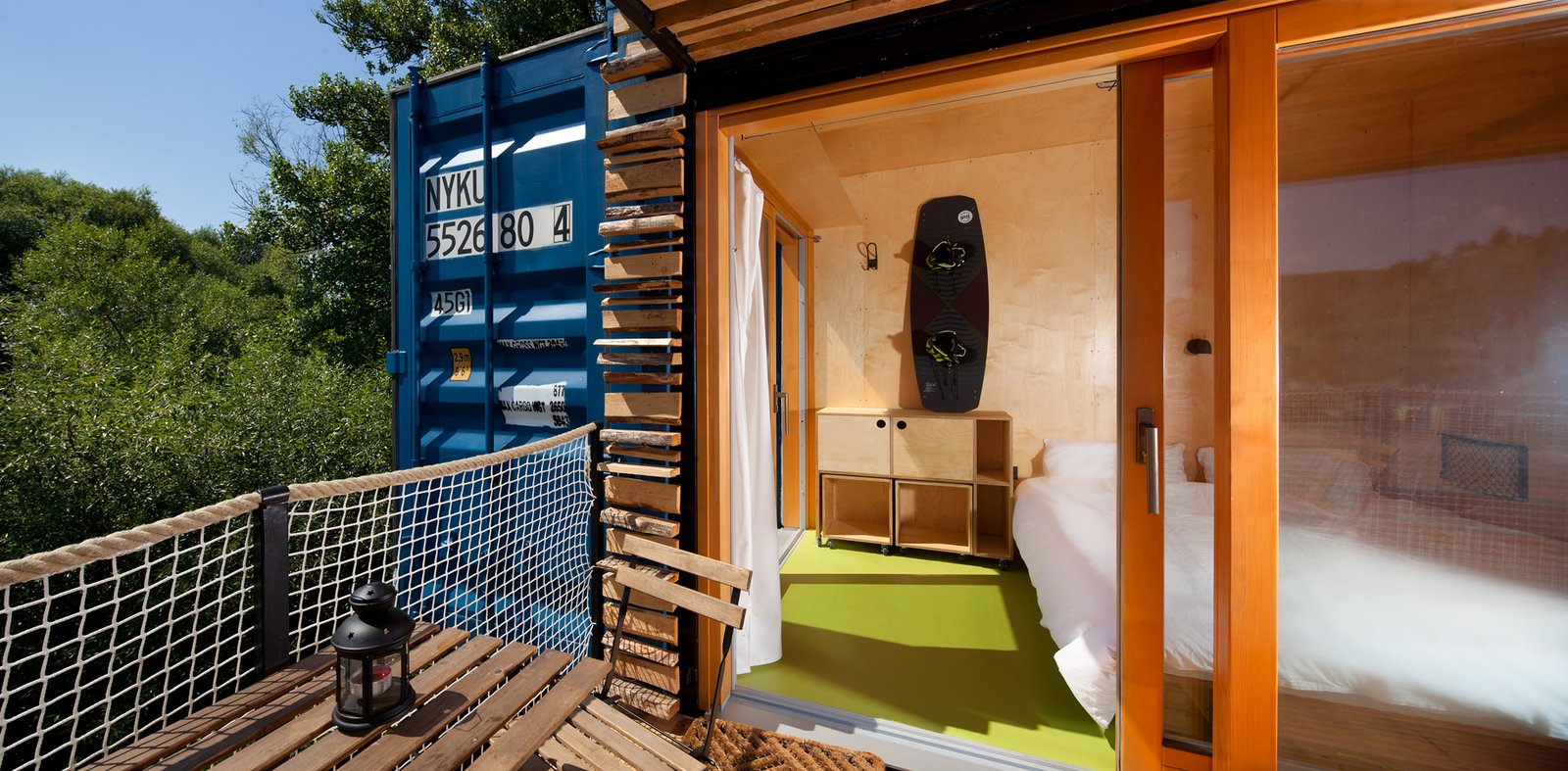 Bed, Night Stands, Storage, Chair, Linoleum Floor, Exterior, Wood Siding Material, and Metal Siding Material  Photo 8 of 15 in A Mobile Boutique Hotel For the Modern Traveler Made From Shipping Containers