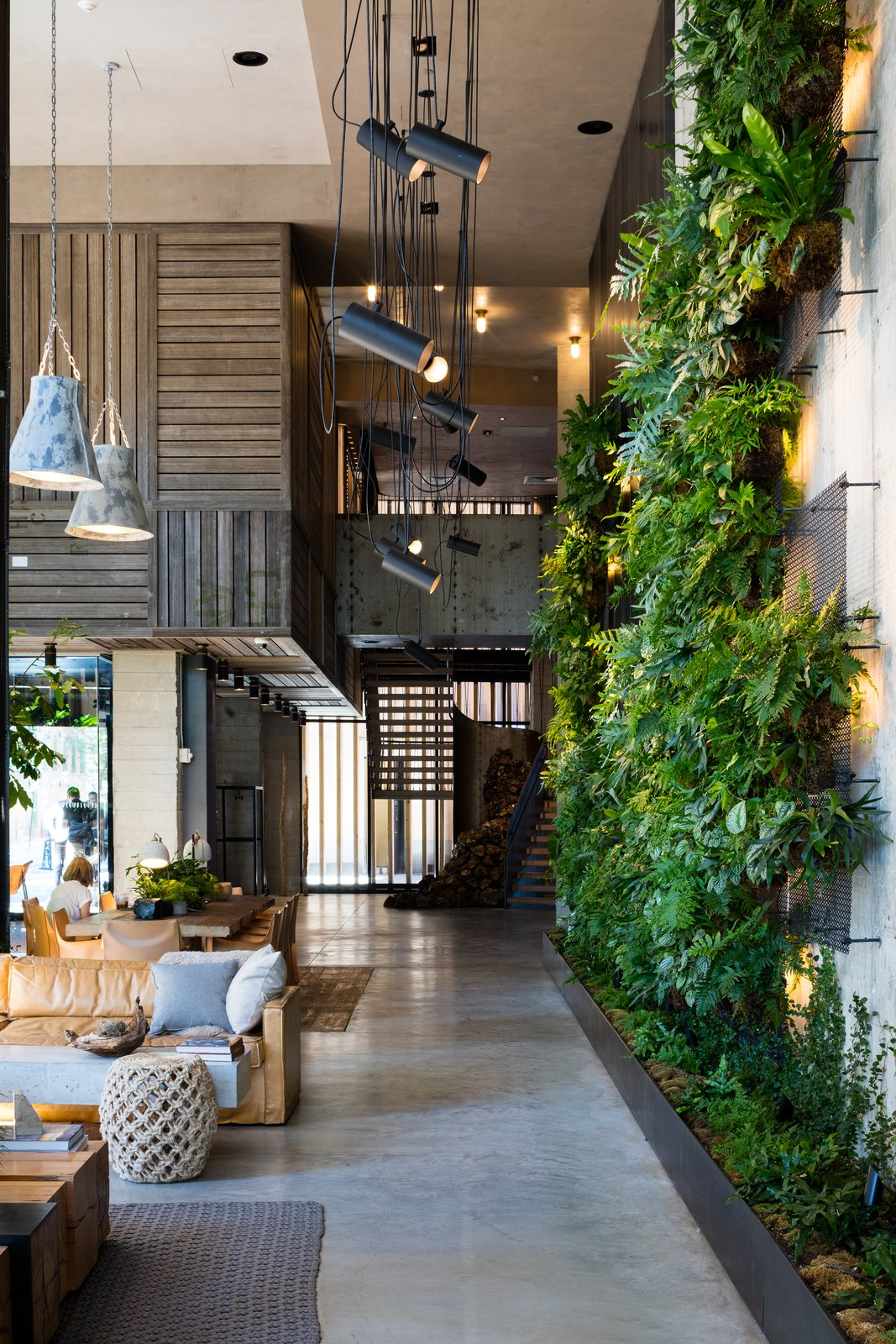 Living Room, Accent Lighting, Console Tables, Sofa, Pendant Lighting, Ceiling Lighting, and Concrete Floor  Photo 5 of 7 in Check Out This Brooklyn Hotel's Dramatic Living Wall Installation