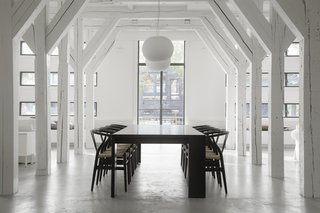 Hans J. Wegner Wishbone Chairs surround the large dining table on axis with the grand, exterior windows.