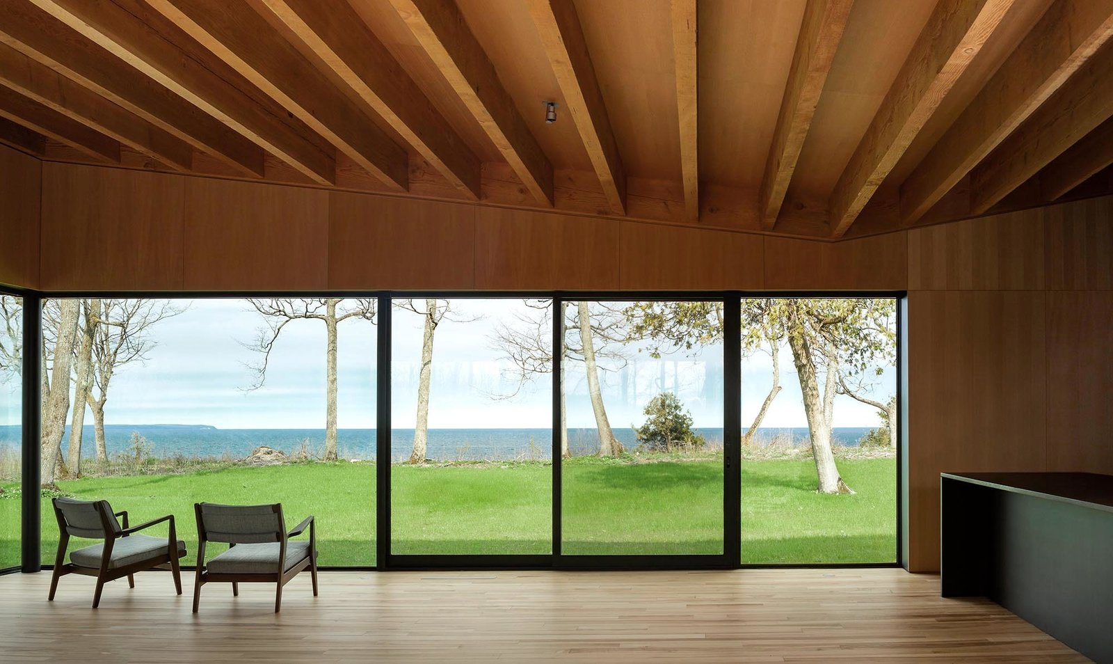 Living Room, Chair, and Light Hardwood Floor  Photo 7 of 12 in A Dramatic Cantilevered Roof Creates a Spacious Terrace Overlooking Lake Michigan