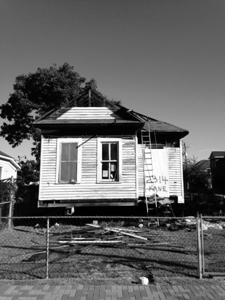 An exterior photograph shows the home at its original location prior to relocation and renovation.