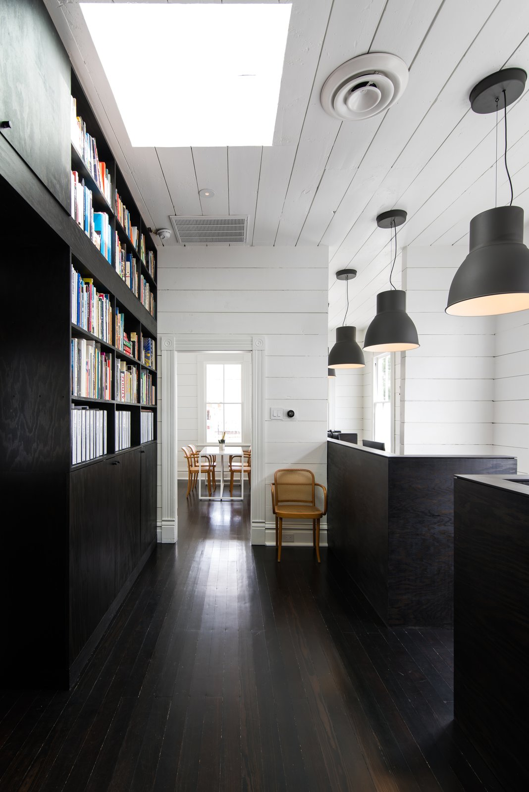 Office, Library Room Type, Chair, Bookcase, Shelves, Desk, Dark Hardwood Floor, and Storage  Photo 11 of 14 in A Victorian Cottage in Houston Finds New Life as a Local Firm's Office