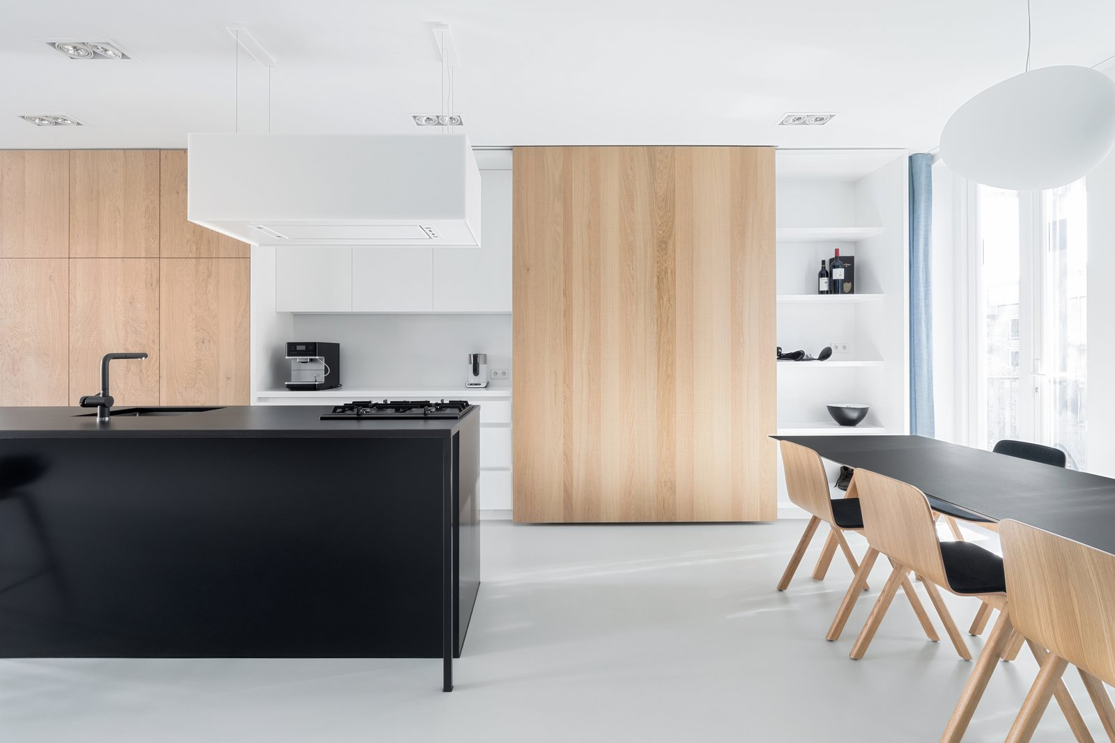 Kitchen, White Cabinet, Wood Cabinet, Ceiling Lighting, Pendant Lighting, Recessed Lighting, and Undermount Sink  Photo 1 of 10 in A Cramped Amsterdam Apartment Is Transformed Into an Airy Loft