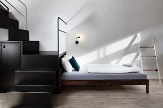 Modern, bent metal stair treads and risers lead to the upper sleeping quarters.