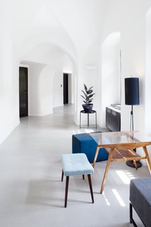 Midcentury modern furniture pieces with blue pastel upholstery and warm, wood tones accent the bright white corridors.
