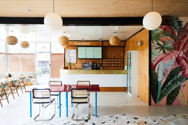 The lobby and reception space is adorned with retro pendant lighting, tropical wall graphics, and colorful furnishings.
