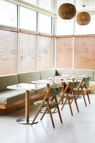 A built-in banquette with light green, tweed patterning is paired with tropical, wooden folding chairs.