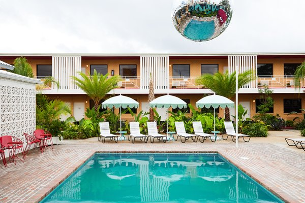 A cantilevered disco ball hangs over the courtyard pool, while guest room balconies overlook the shared communal space. What was previously a concrete parking lot has been transformed into a lush, tropical courtyard.