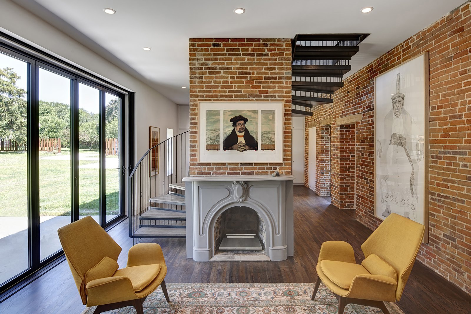 Living Room, Standard Layout Fireplace, Dark Hardwood Floor, Ceiling Lighting, Recessed Lighting, and Chair  Photo 6 of 13 in An 1850s Farmhouse in Iowa City Gets a Modern Makeover