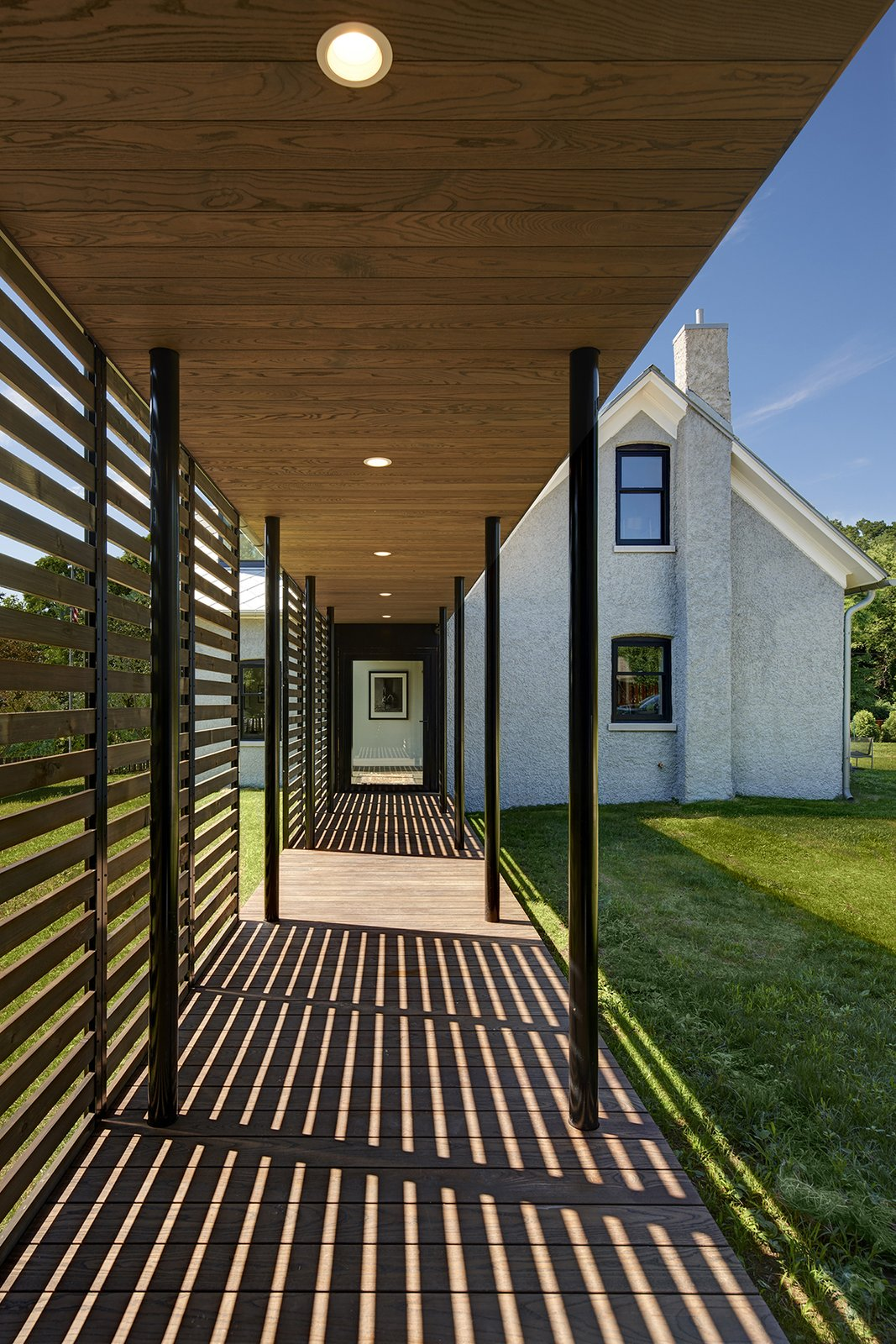 Outdoor, Walkways, Back Yard, Side Yard, Grass, Horizontal Fences, Wall, Wood Fences, Wall, and Decking Patio, Porch, Deck  Photo 5 of 13 in An 1850s Farmhouse in Iowa City Gets a Modern Makeover