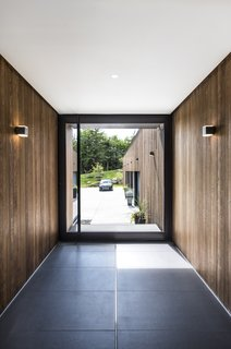 Cedar walls and Bega wall sconces seamlessly extend from exterior to interior.