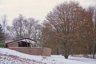 You Can Now Rent Frank Lloyd Wright's Gloriously Restored Eppstein House - Photo 1 of 13 - A curved concrete block wall conceals one of the three exterior terraces.  Low-slung roofs appear to hover above the landscape.