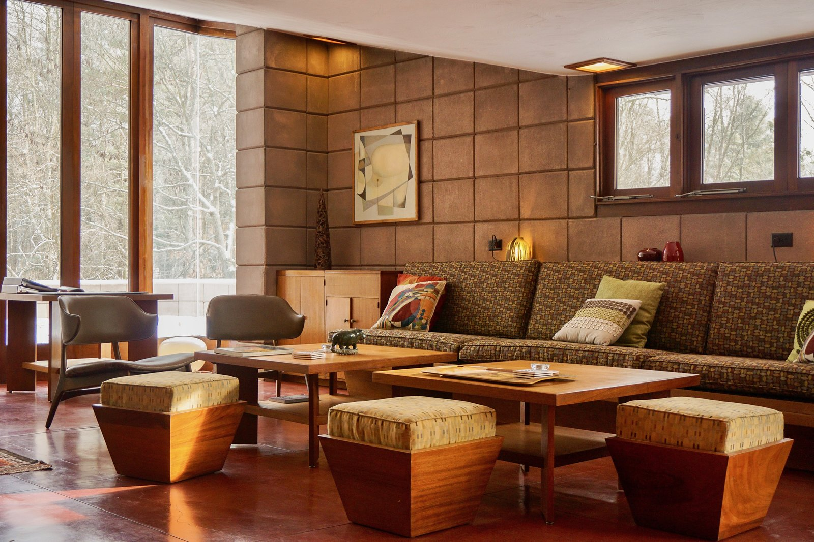 Living Room, Ottomans, Coffee Tables, Chair, Bench, Sofa, Ceiling Lighting, Concrete Floor, Storage, and Table Lighting  Frank Lloyd Wright's Eppstein House from You Can Now Rent Frank Lloyd Wright's Gloriously Restored Eppstein House