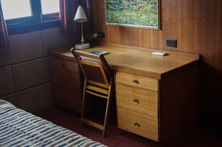 A vintage writer's desk and chair fill the corner of the bedroom.