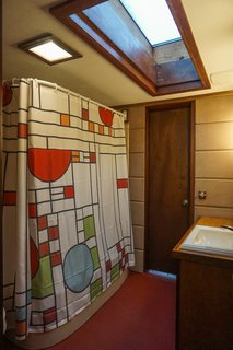 A large, wood-framed skylight fills the master bath with daylight.  A Frank Lloyd Wright-inspired shower curtain accents the remodeled bath.