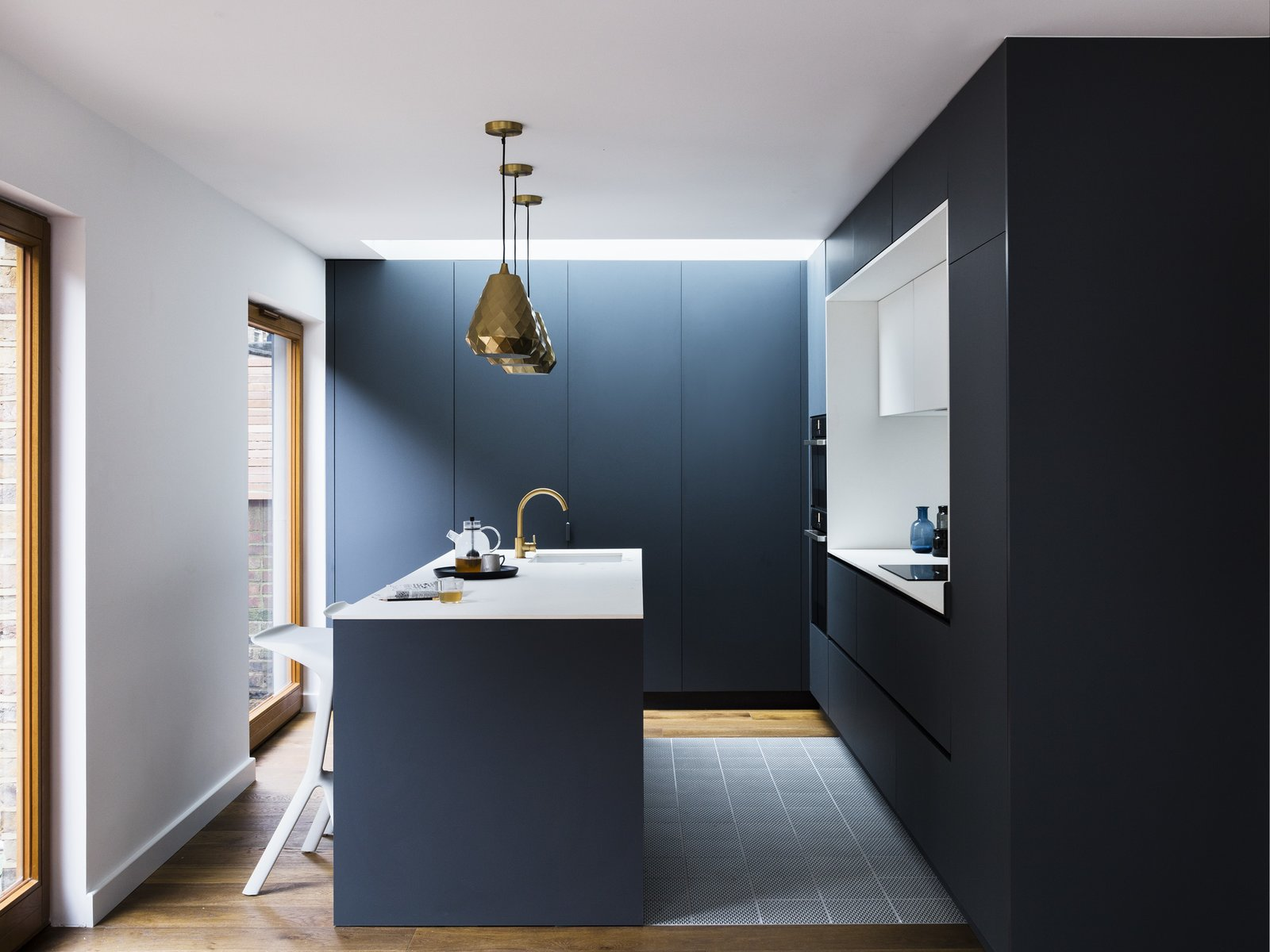 Kitchen, Cooktops, Undermount Sink, Medium Hardwood Floor, White Cabinet, and Pendant Lighting Aston pendants by House Doctor match the metallic hue of the tap.  White Miura Stools be PLANK provide seating at the island.  Photo 7 of 11 in A Sleek Renovation in London Ushers Light Into a Family Home