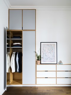 Wardrobe closets display the exposed ply edges, which create a unique outline within the millwork.