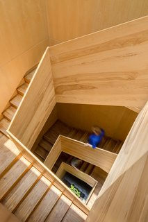 The wood-framed stair extends from the entry way to the rooftop terrace, connecting all levels and spaces. Lit from above, daylight splashes against each floor level.