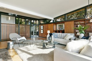Continuous clerestory windows provide views out into the surroundings from all edges. The butterfly roof appears to hover atop the structure.