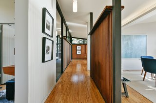 The central gallery, framed by wood screen walls on both sides, links the main living spaces. The partitions create a more open, expansive volume.