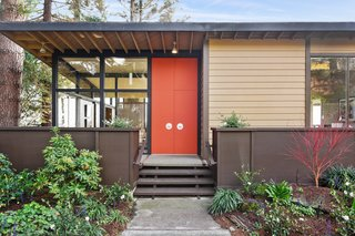 A midcentury modern color palette decorates the exterior. Brightly colored doors highlight the home's entry.