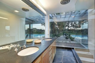 Richard Neutra's Stunning Loring House Is Listed For $5.6M - Photo 5 of 10 - The master bath, a component of the expansion completed by Escher GuneWardena, includes a double vanity, black slate flooring, a walk-in shower, and expansive views of the pool and gardens beyond.