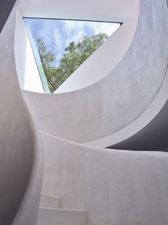 The curvilinear staircase—painted all white—contrasts with the angular forms evident throughout the residence.