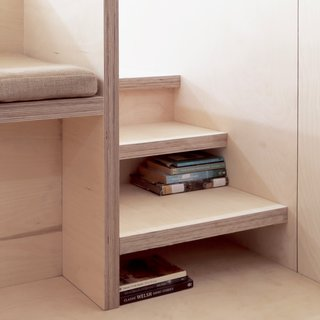 Stairs leading up to the platform bed doubles as storage for books.