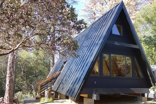 This modern A-frame cabin near Yosemite can accommodate three guests. The A-Frame shape fills the cabin with natural light, and a dark clad exterior contrasts with the warm, honeyed hues of the interior.