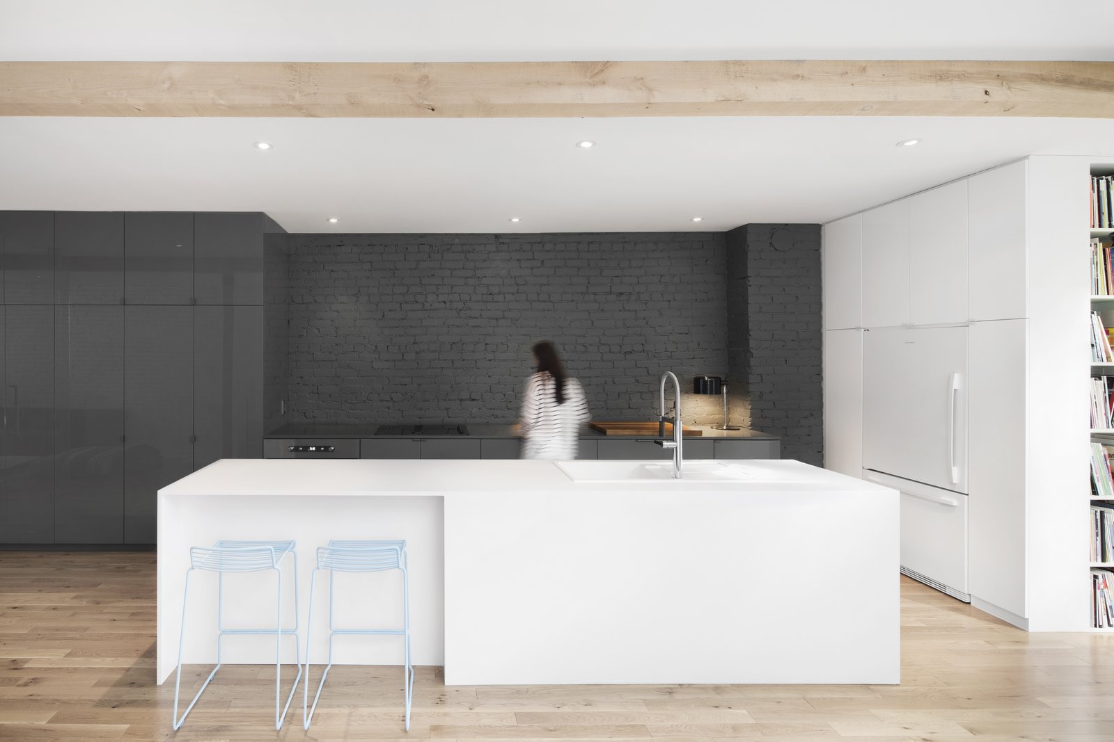 The exterior wall of the kitchen reveals the original brickwork.  Gray, full-height, seamless cabinets match the hue of the gray painted brick. Two light blue counter stools add a pop of color.