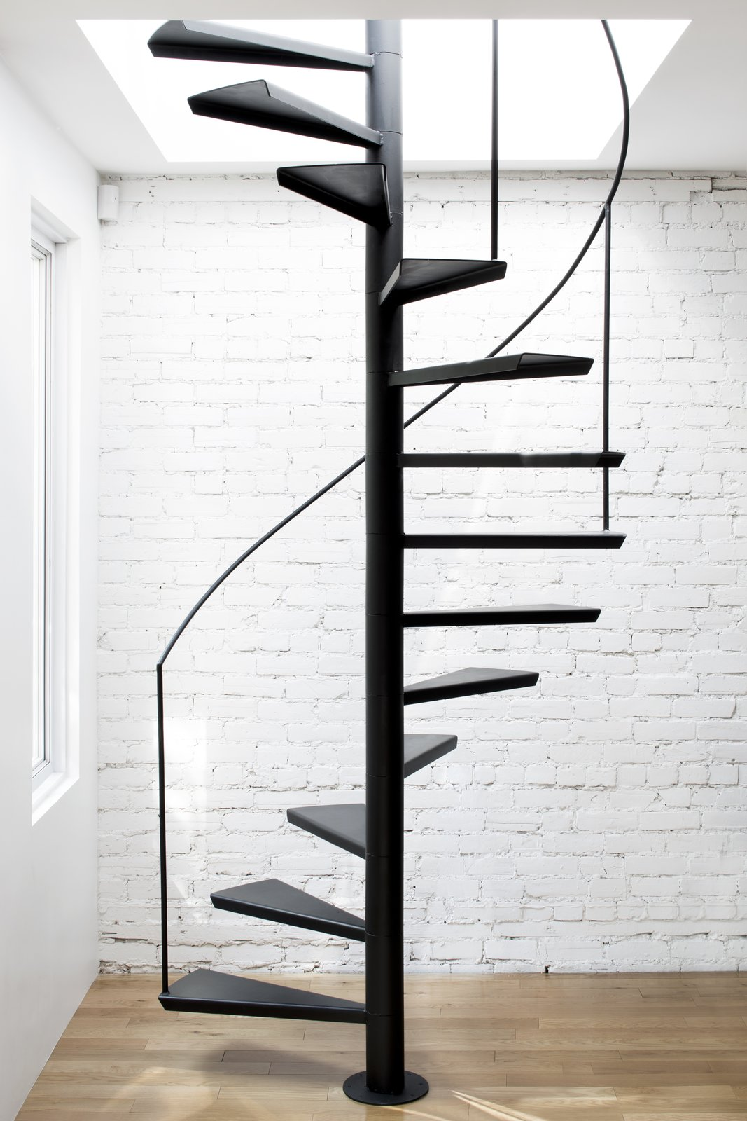 An interior, custom-made steel staircase with floating treads and a minimal handrail, lead to the roof deck above.