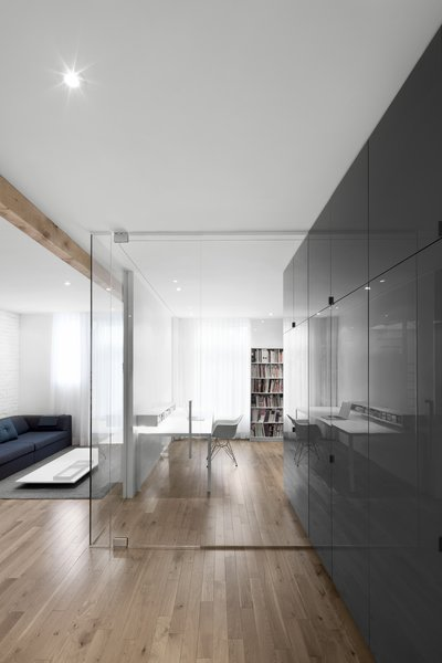 The full-height, gray cabinets extend into the office space, blurring the boundary between workspace and kitchen.  Seamless glazing further increases the transparency between spaces.
